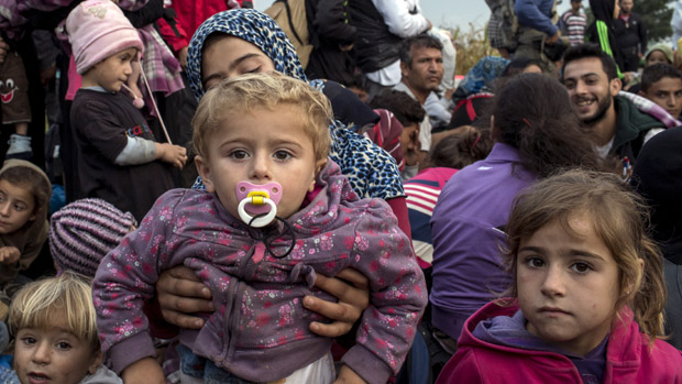 Migrants from Syria wait for a bus after crossing into Hungary from the border with Serbia on a field near the village of Roszke, September 5, 2015. Austria and Germany threw open their borders to thousands of exhausted migrants on Saturday, bussed to the Hungarian border by a right-wing government that had tried to stop them but was overwhelmed by the sheer numbers reaching Europe's frontiers. Left to walk the last yards into Austria, rain-soaked migrants, many of them refugees from Syria's civil war, were whisked by train and shuttle bus to Vienna, where many said they were resolved to continue on to Germany. REUTERS/Marko Djurica - RTX1R9O6
