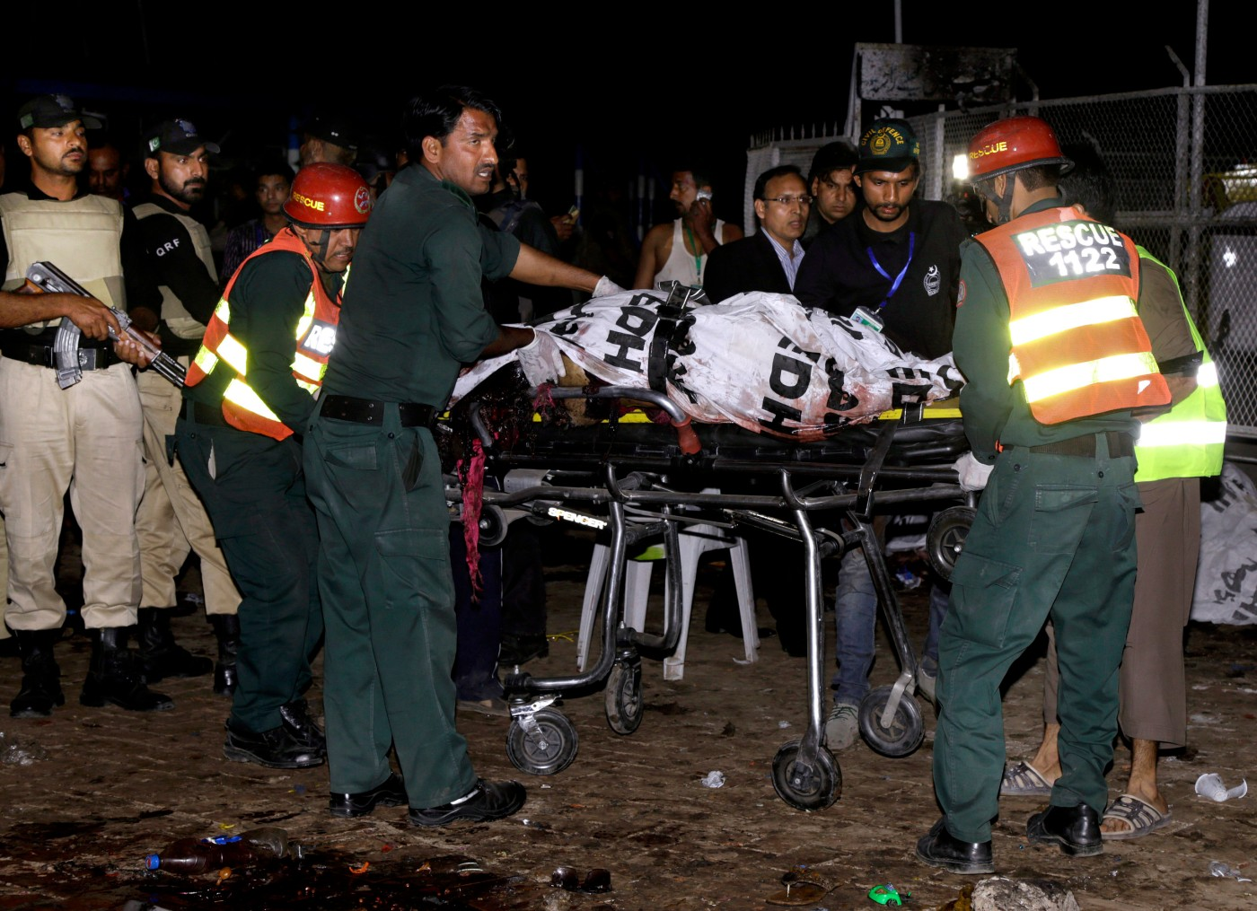 Pakistani rescue workers remove a dead body from the site of bomb explosion in a park in Lahore, Pakistan, Sunday, March, 27, 2016. A bomb blast in a park in the eastern Pakistani city of Lahore has killed tens of people and wounded scores, a health official said. (AP Photo/K.M. Chuadary)